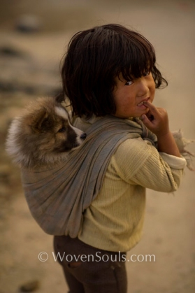 Apatani Tribe child carrying her puppy in the same way that tribal Mothers carry their babies